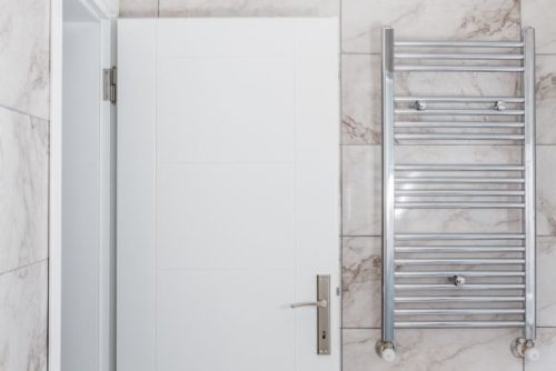 Modern metallic radiator of central heating in bathroom